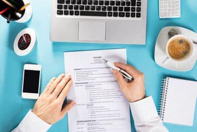 businessman-reading-resume-on-office-desk-859833350-5ad0102318ba0100372d1d06